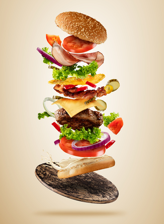 Flying burger ingredients above wooden board on brown background. Concept of low gravity motion and meal preparation. Extra high resolution