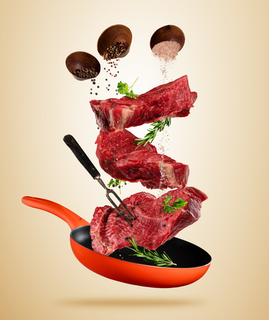 Flying raw steaks, with ingredients for cooking, from pan. wooden bowls with spices. Concept of food preparation. Separated on brown background. Extra high resolution