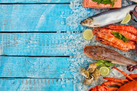 Many kind of seafood, crab, mussels, prawns, fish, salmon steak, mackerel and other shells served on crushed ice and wooden table Stock Photo