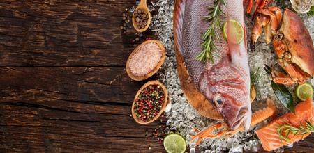 Pargo rojo entero con mariscos, mejillones, gambas, filete de salmón y otras conchas servidas sobre hielo picado y mesa de madera Foto de archivo - 78700843