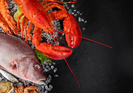 Whole lobster with seafood, crab, mussels, prawns, fish, salmon steak, mackerel and other shells served on crushed ice and black slate Imagens - 78700845
