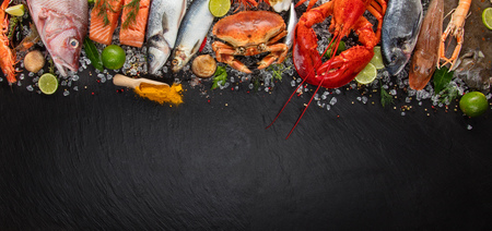 Whole lobster with seafood, crab, mussels, prawns, fish, salmon steak, mackerel and other shells served on black slate stone Banco de Imagens - 78700846