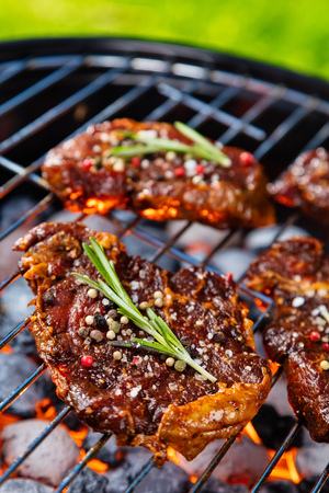 Beef steaks on the grill grate with fiery coals. Barbecue, grill and food concept.