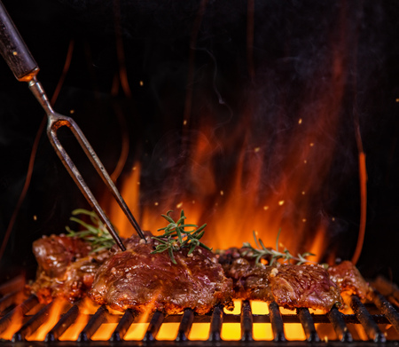 Beef raw steaks on the grill grate with fork, flames on background. Barbecue and grill, delicious food. Stock Photo