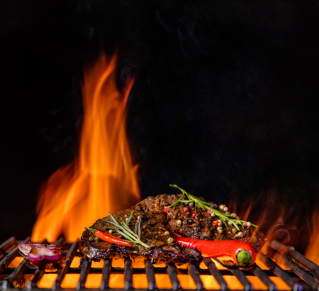 Beef steaks on the grill grate, flames on background. Barbecue and grill, delicious food. Stock Photo