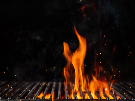 Empty flaming charcoal grill with open fire, ready for product placement. Concept of summer grilling, barbecue, bbq and party. Black copyspace