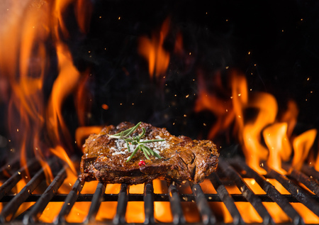 Beef steak on the grill grate, flames on background. Barbecue and grill, delicious food. Stock Photo