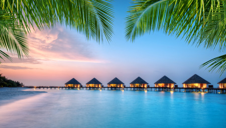 Water villas in lagon, Maldives resort island in sunset. Detail of palm leaves on foreground. Vacation and beach relaxation, summer holidays background
