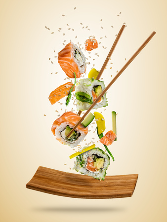 Flying sushi pieces served on plate, separated on colored background. Many kinds of popular sushi food with chopsticks. Concept of flying asian dish with ingredients