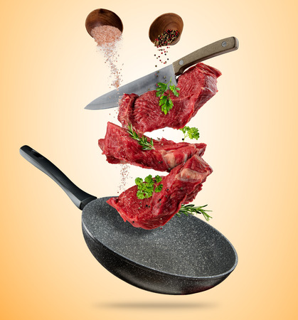 gravedad: Flying raw steaks, with ingredients for cooking, from pan. wooden bowls with spices. Concept of food preparation. Separated on brown background. Extra high resolution