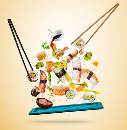 Flying sushi pieces served on wooden plate, separated on colored background. Many kinds of popular sushi food with chopsticks. Concept of flying asian dish with ingredients Stockfoto