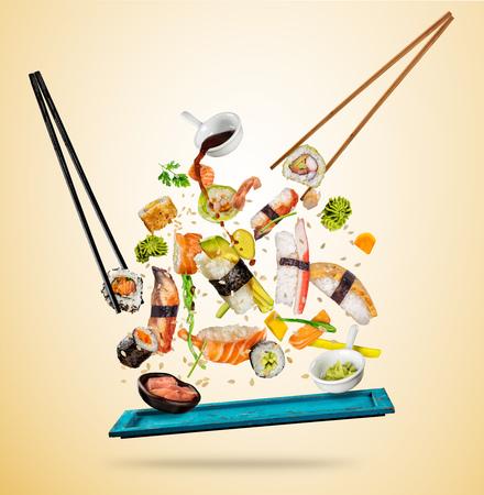 Vliegende sushi stukken geserveerd op houten plaat, gescheiden op gekleurde achtergrond. Veel soorten populair sushi eten met eetstokjes. Concept van vliegende Aziatische gerecht met ingrediënten