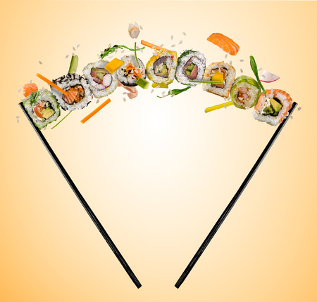 Sushi pieces placed between chopsticks, separated on colored background. Popular sushi food. Flying rice above.