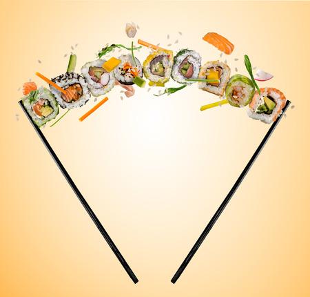 Sushi stukken geplaatst tussen stokjes, gescheiden op gekleurde achtergrond. Populair sushi eten. Vliegende rijst hierboven.