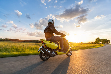 Motorbiker riding on empty road with sunset light, concept of speed and touring in nature. Small motorcycle scooter Stock Photo