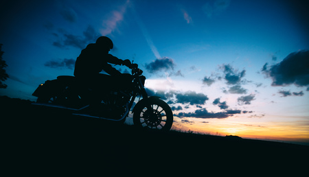 Dark motorbiker silhouette riding high power motorbike in nature with beautiful sunset sky. Travel and transportation. Freedom of motorbike riding