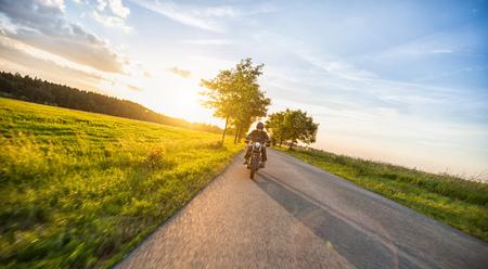 美しい夕焼けの光と自然の中のハイパワー バイクに乗って暗いライディング。旅行と交通。バイク乗りの自由