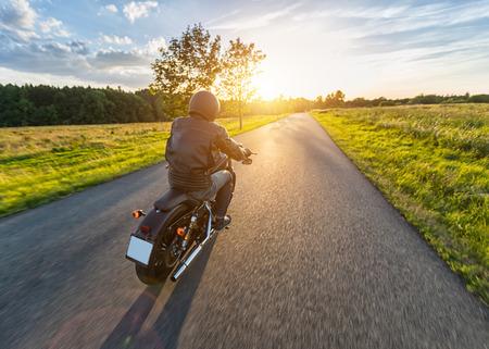 아름 다운 석양 빛과 자연에서 높은 전원 오토바이 타고 어두운 motorbiker. 여행 및 교통. 오토바이 타기의 자유
