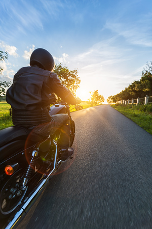 Dark motorbiker riding high power motorbike in nature with beautiful sunset light. Travel and transportation. Freedom of motorbike riding Stock Photo