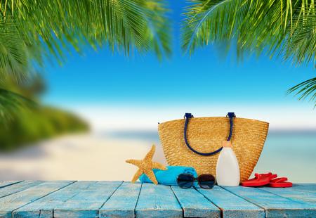 Spiaggia tropicale con accessori per prendere il sole posati su tavole di legno blu, sfondo vacanza estiva. Viaggi e vacanze in spiaggia, spazio libero per il testo.