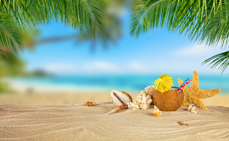 Tropical beach with sea star and coconut drink on sand, summer holiday background. Travel and beach vacation. Stock Photo