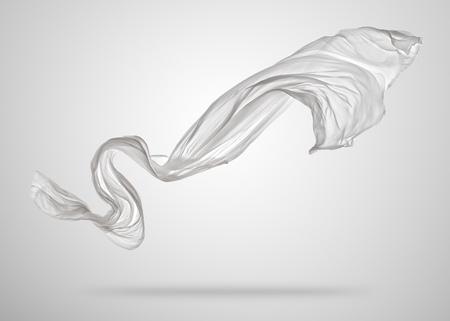 滑らかなエレガントな白い透明な布は、灰色の背景上で区切られます。飛んでファブリックのテクスチャです。
