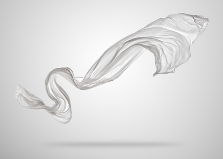 Smooth elegant white transparent cloth separated on grey background. Texture of flying fabric.