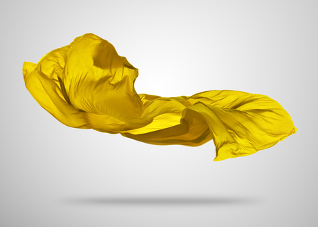 Smooth elegant gold transparent cloth separated on gray background. Texture of flying fabric.