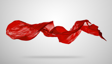 Smooth elegant red transparent cloth separated on grey background. Texture of flying fabric.