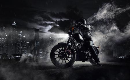 夜人ライダーとハイパワー バイク チョッパーのディテール。近代都市ドバイと霧の背景にバックライト付き。