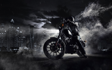 Detail of high power motorcycle chopper with man rider at night. Modern city of Dubai and fog with backlights on background. Stock Photo - 80901327