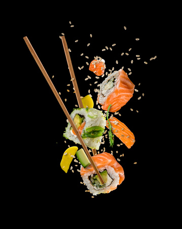 Sushi pieces placed between chopsticks, separated on black background. Popular sushi food.