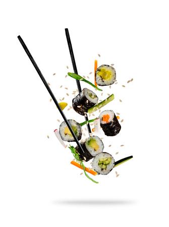 Sushi stukken geplaatst tussen eetstokjes, gescheiden op een witte achtergrond. Populair sushi eten. Stockfoto