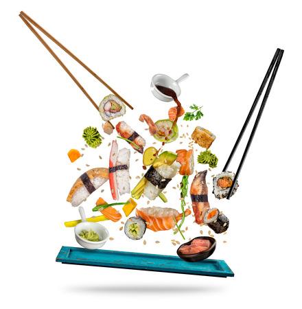 Sushi-Stücke zwischen Stäbchen, getrennt auf weißem Hintergrund. Beliebtes Sushi Essen. Standard-Bild - 80901330