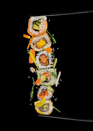箸、黒い背景に区切られた間に、寿司と寿司が配置されます。人気の寿司料理。