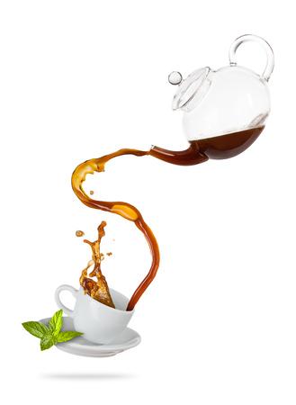 Porcelaine witte kop met spattende thee van kruik, gescheiden op witte achtergrond. Warm drankje met plons, drankjes en verfrissing. Zeer hoge resolutie afbeelding