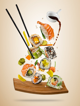 Flying sushi pieces served on wooden plate, separated on soft background. Many kinds of popular sushi food with chopsticks. Very high resolution image Stock Photo