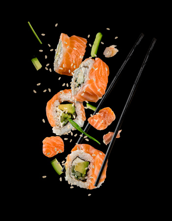 Sushi pieces placed between chopsticks, separated on black background. Popular sushi food. Very high resolution image
