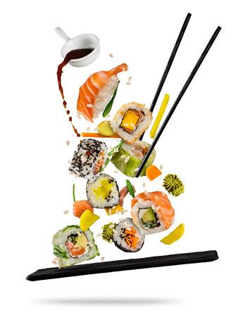 Sushi stukken geplaatst tussen eetstokjes, gescheiden op een witte achtergrond. Populair sushi eten. Zeer hoge resolutie afbeelding Stockfoto
