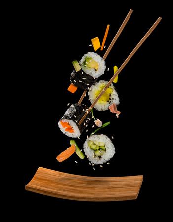 Pièces de sushi placées entre les baguettes, séparées sur fond noir. Aliment de sushi populaire. Image à très haute résolution Banque d'images