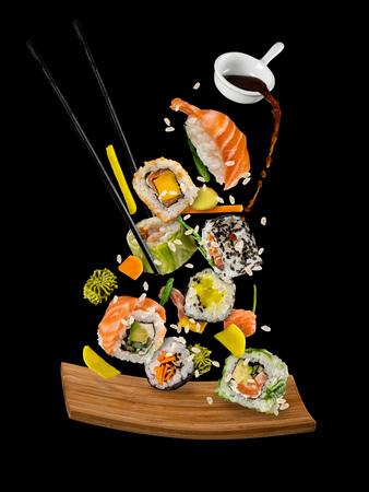 Sushi stukken geplaatst tussen eetstokjes, gescheiden op zwarte achtergrond. Populair sushi eten. Zeer hoge resolutie afbeelding