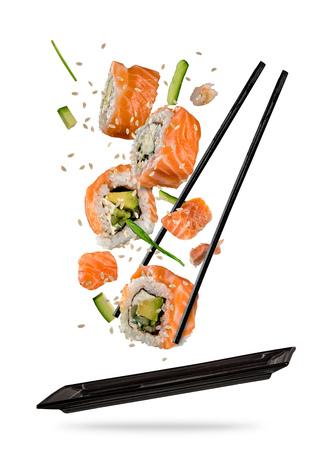 Pièces de sushi placées entre les baguettes, séparées sur fond blanc. Aliment de sushi populaire. Image à très haute résolution Banque d'images