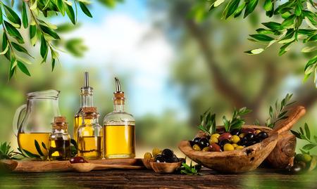 Frisch geerntete Olivenbeeren in Holzschalen und gepresstem Öl in Glasflaschen. Stilleben der Zubereitung von Speisen auf alten Holzbohlen. Freier Platz für Text
