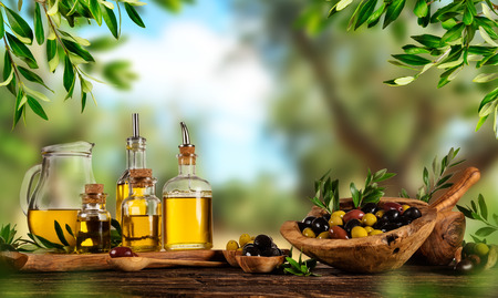 Olives fraîchement récoltées, baies dans des bols en bois et huile pressée dans des bouteilles en verre. Nature morte de préparation de la nourriture servie sur de vieilles planches de bois. Espace libre pour le texte