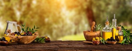 Świeżo zebranych oliwek jagody w miski z drewna i olej prasowany w szklanych butelkach. Wciąż życie karmowy przygotowanie słuzyć na starych drewnianych deskach. Wolne miejsce na tekst