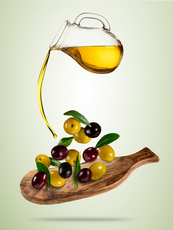 Olive oil with flying olives in wooden bowl, concept of healthy eating. Studio photo in high resolution. Diet and healt eating and lifestyle. Separated on colored background Reklamní fotografie