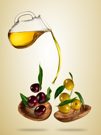 Olive oil with flying olives in wooden bowls, concept of healthy eating. Studio photo in high resolution. Diet and healt eating and lifestyle. Separated on colored background Stock Photo