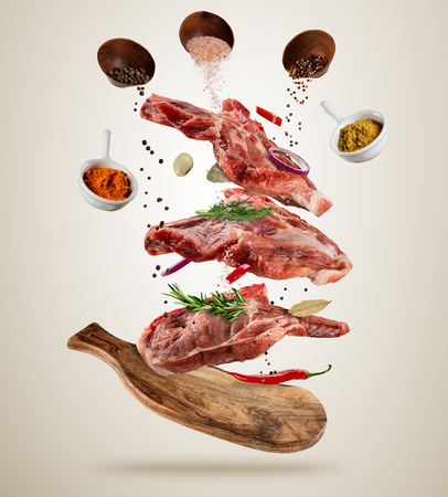 Flying pieces of raw pork steaks, with ingredients for cooking, served on woodenboard. Concept of food preparation in low gravity mode. Separated on soft background. High resolution image 免版税图像