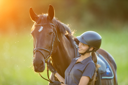 Young woman rider with her horse in evening sunset light. Outdoor photography in lifestyle mood Stock Photo