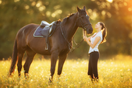 Young woman with her horse in evening sunset light. Outdoor photography with fashion model girl. Lifestyle mood photo